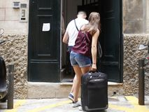 A couple arrives with the suitcases at a hotel Stock Image