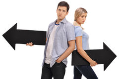 Couple with arrows pointing in the opposite direction. Sad young couple posing with two arrows pointing in the opposite direction isolated on white background stock images