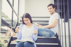 Couple asian handsome man and beautiful woman reading book and smile at home, boyfriend and girlfriend with activities together. Couple asian handsome men and Royalty Free Stock Image