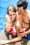 Couple in Asian hotel pool drinking cocktails Stock Photos