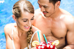 Couple in Asian hotel pool drinking cocktails Royalty Free Stock Images