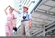 Couple of Asian old man and woman tourist are dancing among the big building of big city. This photo also contain concept of good stock images