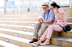 Couple of Asian old man and woman tourist are looking at tablet and acting like get some good news. This photo also contain stock photos