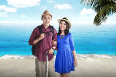Couple asian tourist standing on the beach. With blue sky background Royalty Free Stock Photo