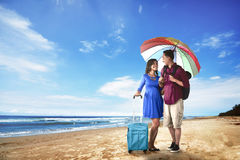 Couple asian tourist standing on the beach. With blue sky background Stock Photography