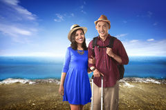 Couple asian tourist standing on the beach. With blue sky background Stock Image
