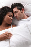 Couple asleep in bed. Happy young couple asleep in bed together Royalty Free Stock Photography