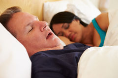 Couple Asleep In Bed With Man Snoring Stock Photos