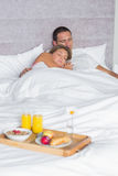 Couple asleep with breakfast tray on bed Royalty Free Stock Photo