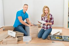 Couple assembling furniture Stock Photos