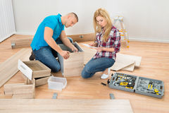 Couple Assembling Wooden Drawers Royalty Free Stock Images