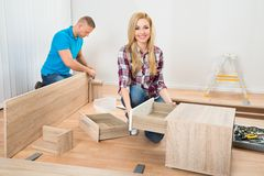 Couple assembling wooden furniture Royalty Free Stock Photography