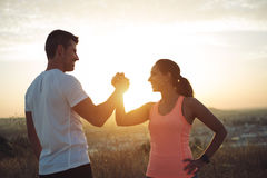 Couple of athletes fiving and success. Couple of athletes giving high five for celebrating outdoor workout goals and success. Man and women training together royalty free stock images