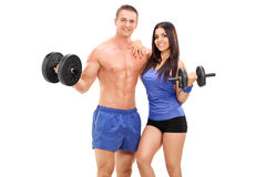 Couple of athletes posing with metal weights Stock Photography