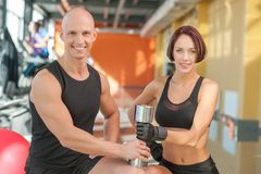 Couple of athletes posing with metal weights at Stock Photography