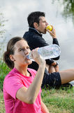Couple of Athletes Resting. A healthy couple drinking water and eating apple for recovering after training Royalty Free Stock Image
