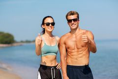 Couple of athletes showing thumbs up on beach Royalty Free Stock Photos
