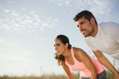 Couple of athletes taking a running workout break Stock Photos