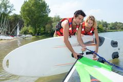 Couple attaching sail to windsurfing board Stock Photo