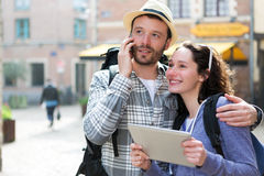 Couple of attractive tourists using tablet and smartphone Royalty Free Stock Images