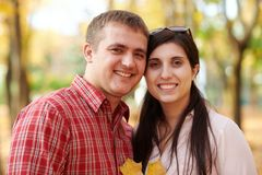 Couple is in autumn city park. Bright yellow trees royalty free stock image