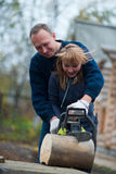 Couple in autumn home garden sawing wood. Middle aged couple in autumn home garden sawing wood Royalty Free Stock Photography