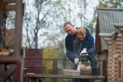 Couple in autumn home garden sawing wood. Middle aged couple in autumn home garden sawing wood Royalty Free Stock Image