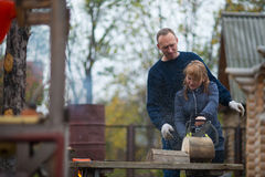 Couple in autumn home garden sawing wood. Middle aged couple in autumn home garden sawing wood Stock Photos