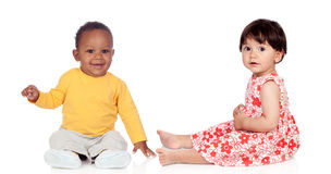 Couple of babies sitting on the floor. Isolated on a white background Stock Images