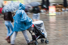 Couple with baby buggy at heavy rain Stock Photo