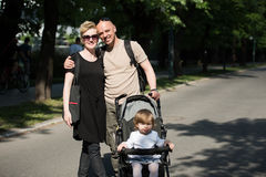 Couple with baby pram in summer park Royalty Free Stock Photography