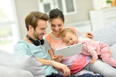 Couple and baby using tablet at home Stock Image