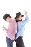Couple back to back with hats and hands gesturing Royalty Free Stock Image