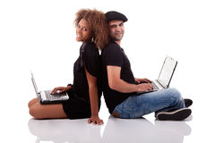 Couple back to back, sitting on the floor. With computers, isolated on white background, studio shot Royalty Free Stock Image