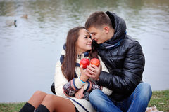 Couple on a background of water in autumn with apples Stock Images