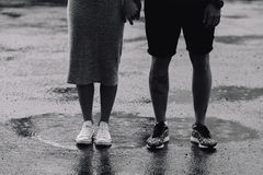 Couple on the background of wet asphalt. Photo of the lower half of the body on the background of a pair of wet asphalt Stock Photo