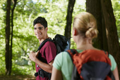 Couple with backpack doing trekking in wood Royalty Free Stock Photos