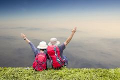 Couple backpack travel relaxing on top of a mountain Stock Photo