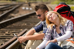 Couple backpack traveling resting on railroad map. Happy direction tired royalty free stock photos