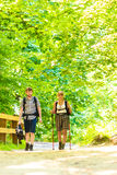 Couple backpacker hiking in forest pathway Stock Images