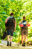 Couple backpacker hiking in forest pathway. Adventure, tourism active lifestyle- young couple backpacker hiking in forest pathway back view Royalty Free Stock Image