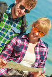 Couple backpacker with map by seaside Royalty Free Stock Photography