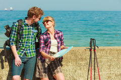 Couple backpacker with map by seaside Royalty Free Stock Photo