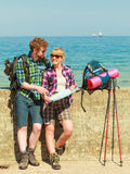 Couple backpacker with map by seaside Stock Photo