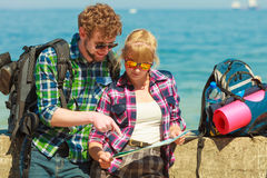 Couple backpacker with map by seaside Royalty Free Stock Photos