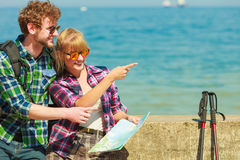 Couple backpacker with map by seaside Stock Photos