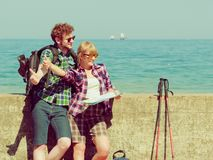 Couple backpacker with map by seaside hitchhiking. Adventure, summer, tourism. Young couple backpacker hitchhiker with map by seaside hitchhiking with thumb up Stock Image