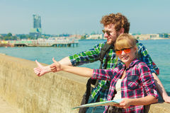 Couple backpacker with map by seaside hitchhiking. Adventure, summer, tourism. Young couple backpacker hitchhiker with map by seaside hitchhiking with thumb up Stock Photography