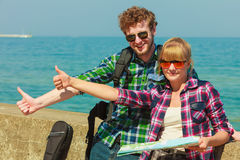 Couple backpacker with map by seaside hitchhiking. Adventure, summer, tourism. Young couple backpacker hitchhiker with map by seaside hitchhiking with thumb up Stock Images