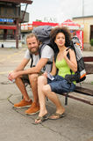A couple of backpacker tourists sitting on a bench Royalty Free Stock Photo